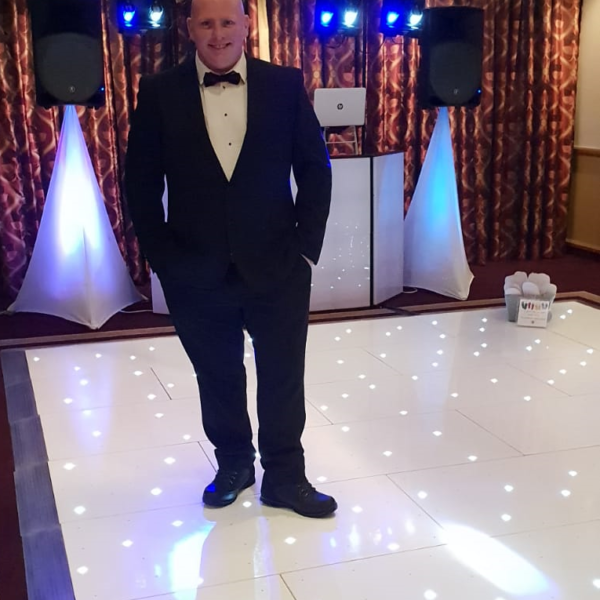 DJ in tux standing on LED disco dance floor for hire