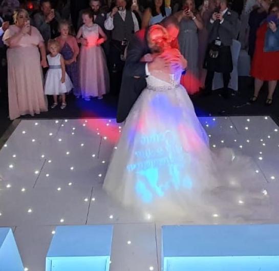 newlyweds enjoying first dance on LED light up dance floor